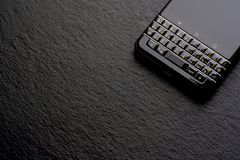 Black business smartphone, shale. High quality close up photo of a modern business smartphone lying on some black stony surface. There is some brutal black Stock Photography