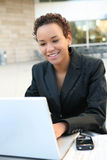 Black Business Woman. A pretty african american business woman on computer stock photos