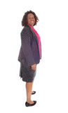 Black business woman. An African American business woman standing in profile isolated for white background and smiling stock photography
