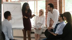 Black business woman coach training team giving flip chart presentation
