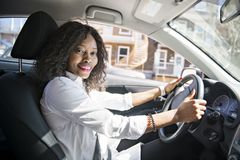 Black Business woman on a white car. A black business woman on a white car royalty free stock images