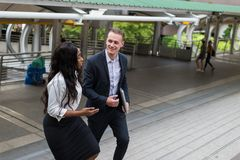 Black businesswoman and Caucasian businessman walking in the city and talk about business plan in the future. Black business women and Caucasian businessman royalty free stock photography