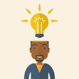 Black businessman with bulb on his head. A black businessman has a bright idea for marketing strategy with a bulb on his head. Human intelligence concept. A Royalty Free Stock Image