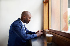 Black businessman in a cafe using cell phone Stock Image