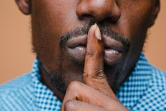Black businessman calls on the silent,  on brown background Stock Image
