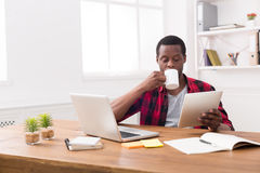 Black businessman in casual office, reading news on tablet, drinking coffee Royalty Free Stock Photography