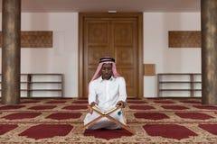 Black Businessman In Dishdasha Is Reading The Quran Royalty Free Stock Photos