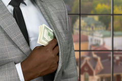 Black businessman hiding cash. Stock Photography