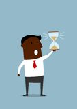 Black businessman with hourglass in hand Stock Photos