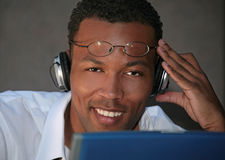Black Businessman Listening to Music With Headphon Stock Photo