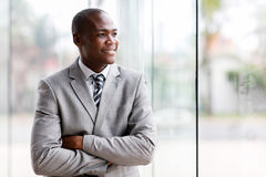 Black businessman looking. Handsome black businessman looking outside window stock photography
