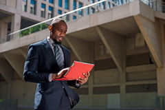 Black businessman looking at his tablet computer in urban backgr Royalty Free Stock Photography