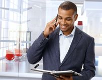 Black businessman on the phone in office lobby Stock Images