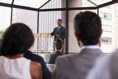 Black businessman presenting business seminar to an audience Royalty Free Stock Photos