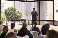 Black businessman presenting seminar gesturing to audience stock photo
