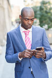 Black businessman reading his smartphone in urban background Stock Photo
