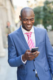 Black businessman reading his smartphone in urban background Royalty Free Stock Photo