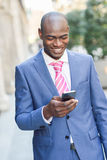 Black businessman reading his smartphone in urban background Royalty Free Stock Photos
