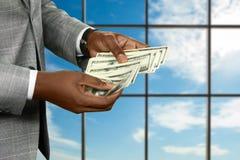 Black businessman's hand counts money. Stock Photos