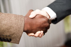 Black businessman shaking hands with a caucasian one Stock Photo