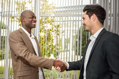 Black businessman shaking hands with a caucasian one Stock Images