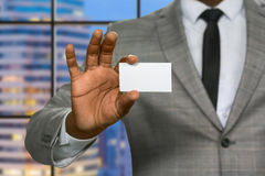 Black businessman shows visit card. Royalty Free Stock Images
