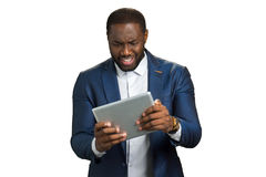 Black businessman surprised looking at computer tablet. Stock Photos