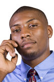 Black Businessman talking on a cell phone. Isolated Black businessman with his hand in pocket talking on the phone Stock Images