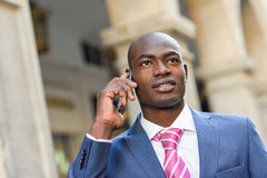 Black businessman talking with his smart phone in urban backgrou Stock Photos