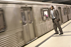 Black Businessman Watching the Metro Train Pass Royalty Free Stock Image