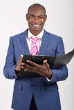 Black businessman wearing suit and tie smiling. Portrait of black businessman wearing suit and tie smiling on white background with a black folder in his hands Stock Photos