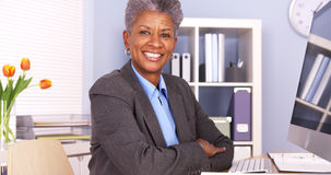 Black businesswoman sitting at desk smiling Stock Photography