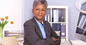 Black businesswoman sitting at desk smiling Royalty Free Stock Images