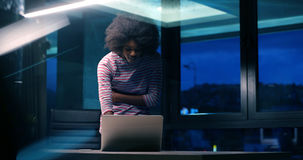 Black businesswoman using a laptop in night startup office Stock Photo