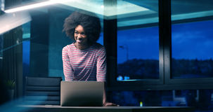 Black businesswoman using a laptop in night startup office Royalty Free Stock Photos