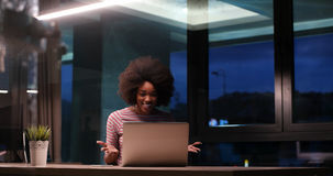 Black businesswoman using a laptop in night startup office Royalty Free Stock Images