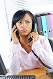 Black businesswoman using two phones at desk Royalty Free Stock Photos