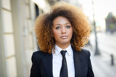 Black businesswoman wearing suit and tie in urban background Royalty Free Stock Photography