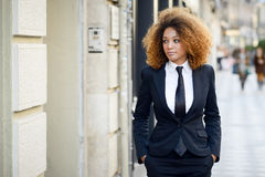 Black businesswoman wearing suit and tie in urban background. Portrait of beautiful black businesswoman wearing suit and tie in urban background. Model of royalty free stock photography