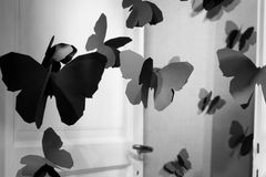 Black Butterflies. Floating Black Paper Cut-Out Butterflies Flying Through A Door Royalty Free Stock Photos