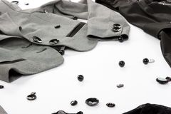 Black buttons with parts of clothes. Over white background Royalty Free Stock Photography