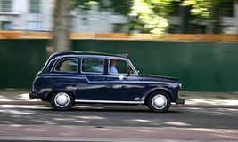 Black Cab. London Taxi car with motion blur effect stock photography