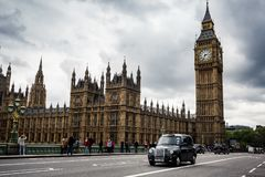 Black cab passes pedestrians walking in front of Big Ben and Houses of Parliament on Westminster Bridge.n Stock Images
