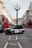 A Black Cab in Regent Street, London. A Black Cab in Regent Street in London. The London's iconic black cabs are a symbol of the city and a major attraction in royalty free stock image