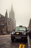 Black cab at the strret in Edinburgh, UK. EDINBURGH, UK - SEPTEMBER 15, 2014: Typical black cab at the street of the city center. Cloudy weather, old vintage Royalty Free Stock Images