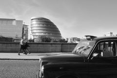 Black cab in traffic jam. Street scene shot on Tower Bridge in London: a black cab stuck in slow traffic, while pedestrians are passing by. Black and white, BW stock photography