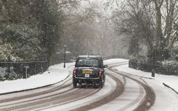 Black cab in winter white London. LONDON, UK – MAR 2018: Black cab driving on snow-covered road in north London royalty free stock image