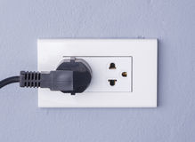 Black cable plugged in a white electric outlet mounted on gray w Stock Photography