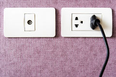 black cable plugged in a white electric outlet mounted on pink w Stock Images