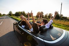 Black cabriolet is on the country road. Happy group of young girls and guys are sitting in the car hold their hands up stock photo